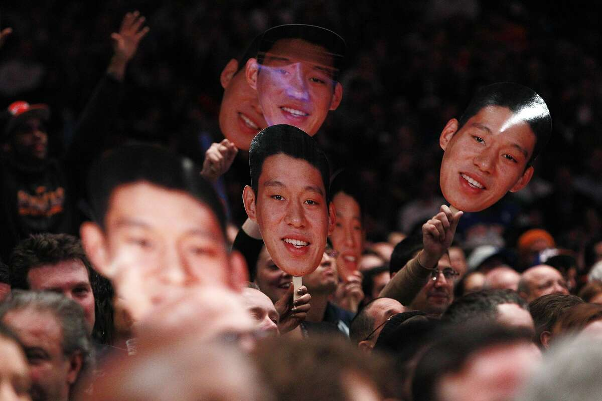 FILE - In this Feb. 15, 2012, file photo, fans hold up New York Knicks' Jeremy Lin photos during the second half of an NBA basketball game against Sacramento in New York. Linsanity is finally getting another run on MSG Network. In search of content to fill with no games because of the coronavirus, the network is turning to Jeremy Lin's memorable NBA breakthrough, which was once ratings gold. The network said Friday, April 24, 2020 it will dedicate a week of programming to the 2012 stretch when Lin got his chance with the New York Knicks and took the league by storm.(AP Photo/Frank Franklin II, File)