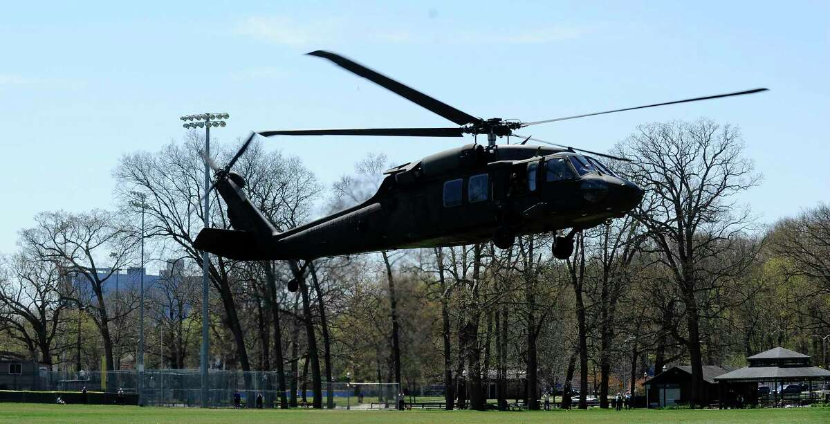 Stamford residents check out a Connecticut National Guard UH-60 Blackhawk helicopter, that landed at Scalzi Park in Stamford, Connecticut on Saturday, April 25, 2020. The crew from the 169th Aviation Unit out of Hartford, brought Brigadier General Ralph Hedenberg, Connecticut's Director, Joint Staff, and members of his staff to check in with troops and medical staff at Stamford Hospital. Members of the Connecticut National Guard have been deployed at Stamford Hospital, repurposing a building on the site to help meet any extra demand brought on by the coronavirus pandemic. The general spent about 4 hours visiting with medical crews that include 85 Army reservists and nine state guardsmen, as well as the medical staff at Stamford Hospital, before returning Scalzi Park for a 30 minute flight back to Hartford's Bradley Airport. Hundreds of residents gathered at the park to show their support, waving as the Blackhawk, piloted by 1st Lt. Grant Arnold, U.S. Army CT National Guard, took to the skies.
