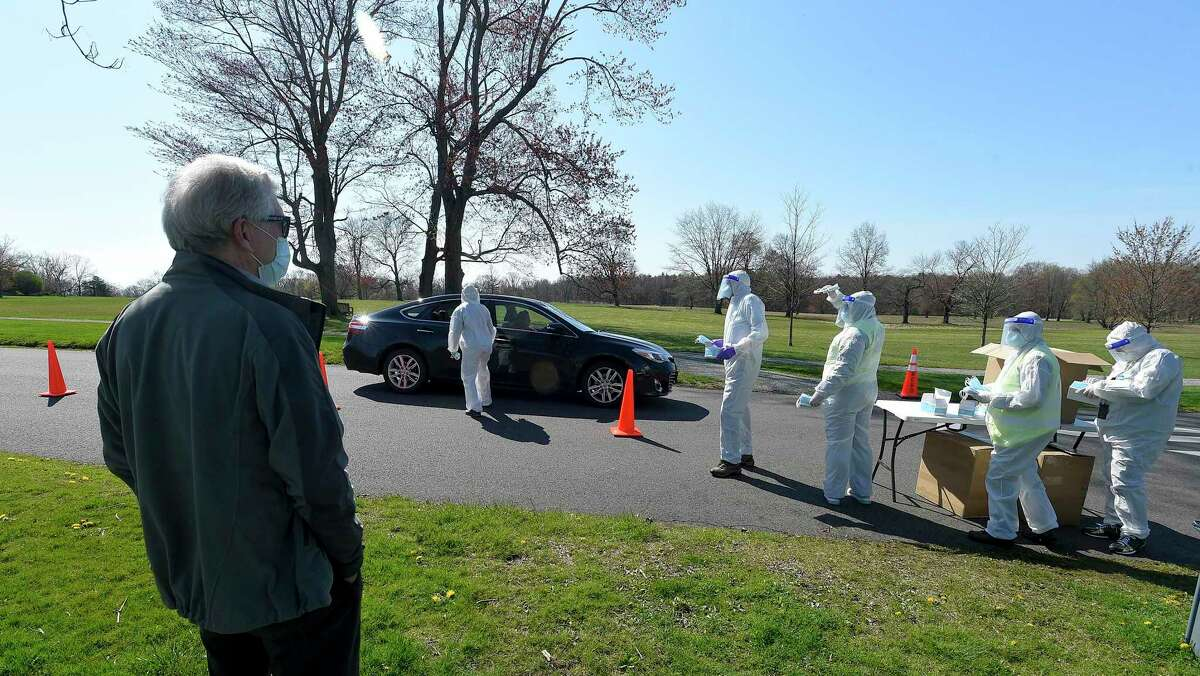 New Canaan First Selectman Kevin Moynihan watches as volunteer's from New Canaan's Community Emergency Response Team (CERT) handout masks to residents during a Community Mask Distribution at Waveny Park in New Canaan, Connecticut on Saturday, April 25, 2020. Some 30 volunteers in protective suits, gloves, masks and face shields (PPE's) handed out over 30,000 masks.
