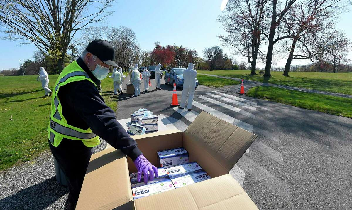 Volunteers from New Canaan's Community Emergency Response Team, (CERT), hand out face masks to residents during a Face Mask Distribution at Waveny Park in New Canaan recently. Some 30 volunteers in protective suits, gloves, face masks, and face shields, (PPE - Personal Protective Equipment), handed out over 10,000 face masks. The town's Director of Emergency Management Michael Handler spoke about what wearing a face mask in the town amid the coronavirus pandemic means, in his Wednesday night call to town residents about the virus in the town for May 13.