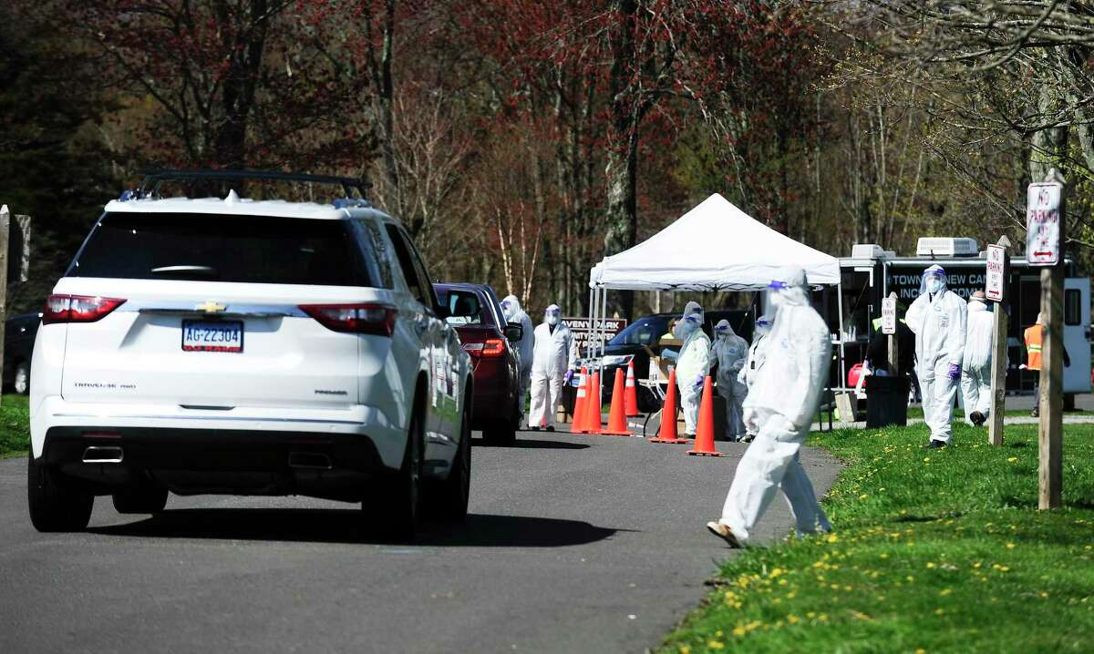 Volunteers from New Canaan's Community Emergency Response Team (CERT) hand out masks to residents during a Community Mask Distribution at Waveny Park in New Canaan, Connecticut on Saturday, April 25, 2020. Some 30 volunteers in protective suits, gloves, masks and face shields (PPE's) handed out over 10,000 masks. Less than one percent of those tested in New Canaan Friday, Nov. 20, were positive for COVID-19, but the virus continues to make inroads back into town, according to First Selectman Kevin Moynihan.