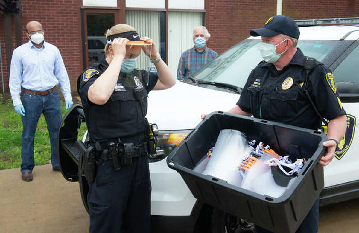 SIUE Police Officer Katie Kircher, left, tries on a face shield, as Sergeant Dan Murphy, right, watches. School of Engineering's Jagath Gunasekera and Brent Vaughn delivered the personal protective equipment.