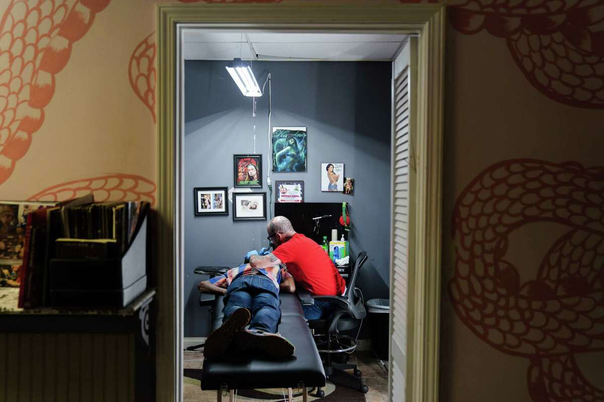 Myke Ršc, 46, who goes by 11Mag, works on a tattoo at Asylum Ink & Art Collective in Atlanta.