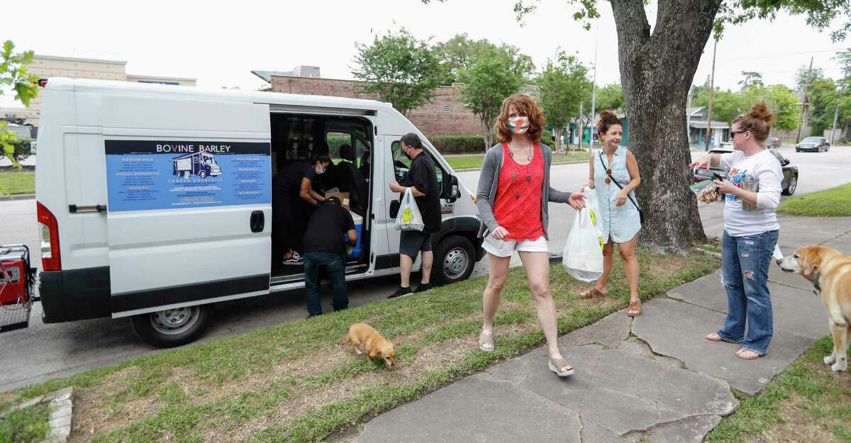 People in the Heights line up to buy frozen cocktails from a Bovine and Barley food truck, in Houston, Saturday, April 25, 2020. The truck features seven different cocktails along with house-made potato chips and salsa.