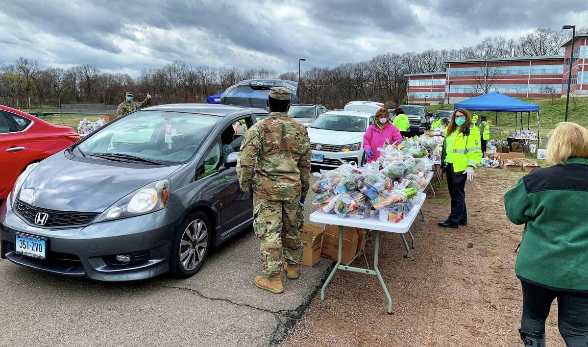 Volunteers and National Guard help load about 400 cars with bags of groceries at drive-thru mobile pantry at Hamden Middle School on April 8. An equal number of cars had to be turned away. |
