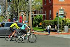 Pedestrians and bikers enjoy the warm weather near downtown Fairfield on Saturday.