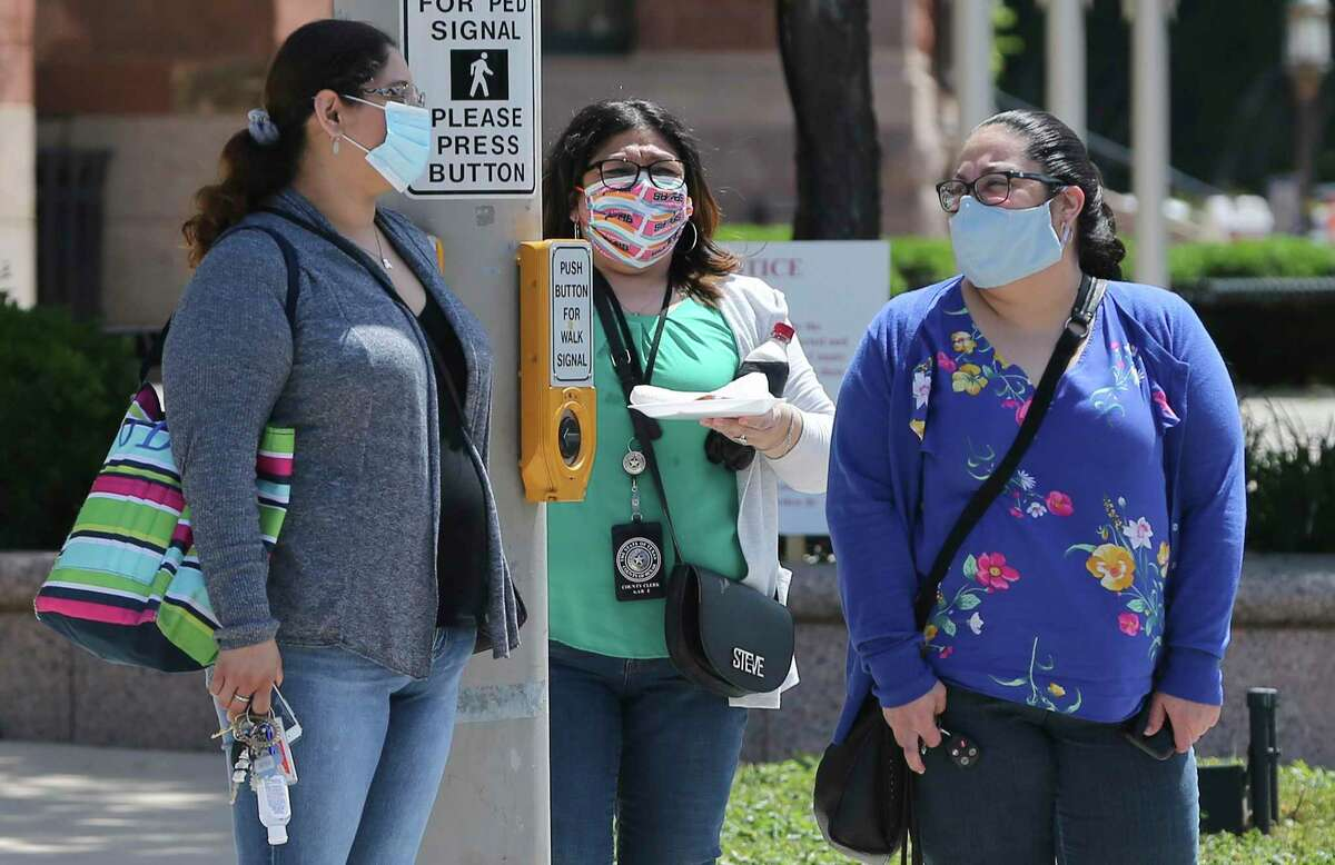 People are seen wearing masks as they leave the Bexar County Justice Center on Monday, Apr. 20, 2020. A city and county order requiring people to wear masks in public took effect on Monday in the continued efforts to stem the spread of the Coronavirus. People are now asked to wear a cloth-type mask whenever they are out in public with the exception of when they're exercising or in their car.