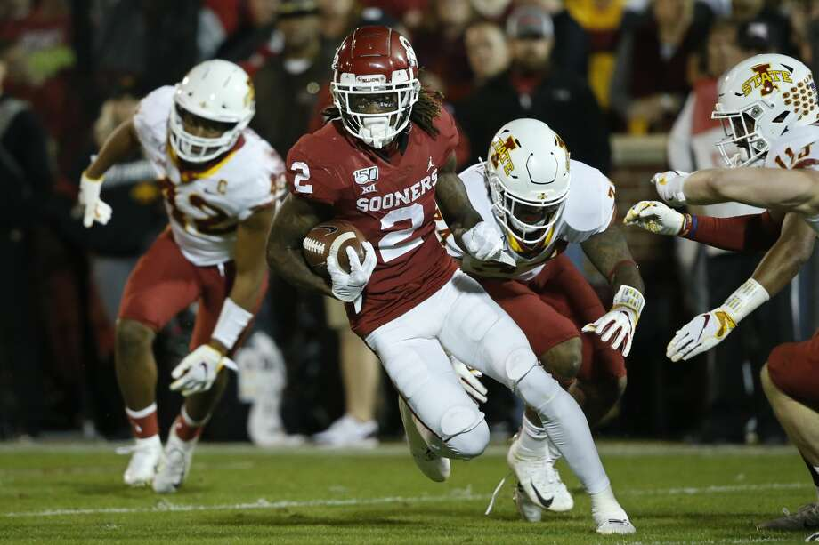 FILE - In this Nov. 9 2019, file photo, Oklahoma wide receiver CeeDee Lamb (2) carries past Iowa State linebacker Marcel Spears Jr., linebacker O'Rien Vance and defensive back Lawrence White, from left, during the first quarter of an NCAA college football game in Norman, Okla. Lamb was selected by the Dallas Cowboys in the first round of the NFL draft. (AP Photo/Sue Ogrocki, File) Photo: Sue Ogrocki,  Associated Press / Copyright 2019 The Associated Press. All rights reserved.