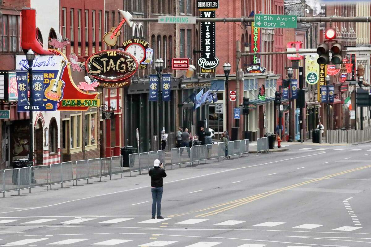 FILE - In this March 23, 2020, file photo, a man stands in the middle of Broadway to take a photo where the streets and sidewalks are normally filled in Nashville, Tenn. Many Nashville musicians have been without steady work for more than five weeks since the city shut down its clubs to slow the spread of the coronavirus. (AP Photo/Mark Humphrey, File)