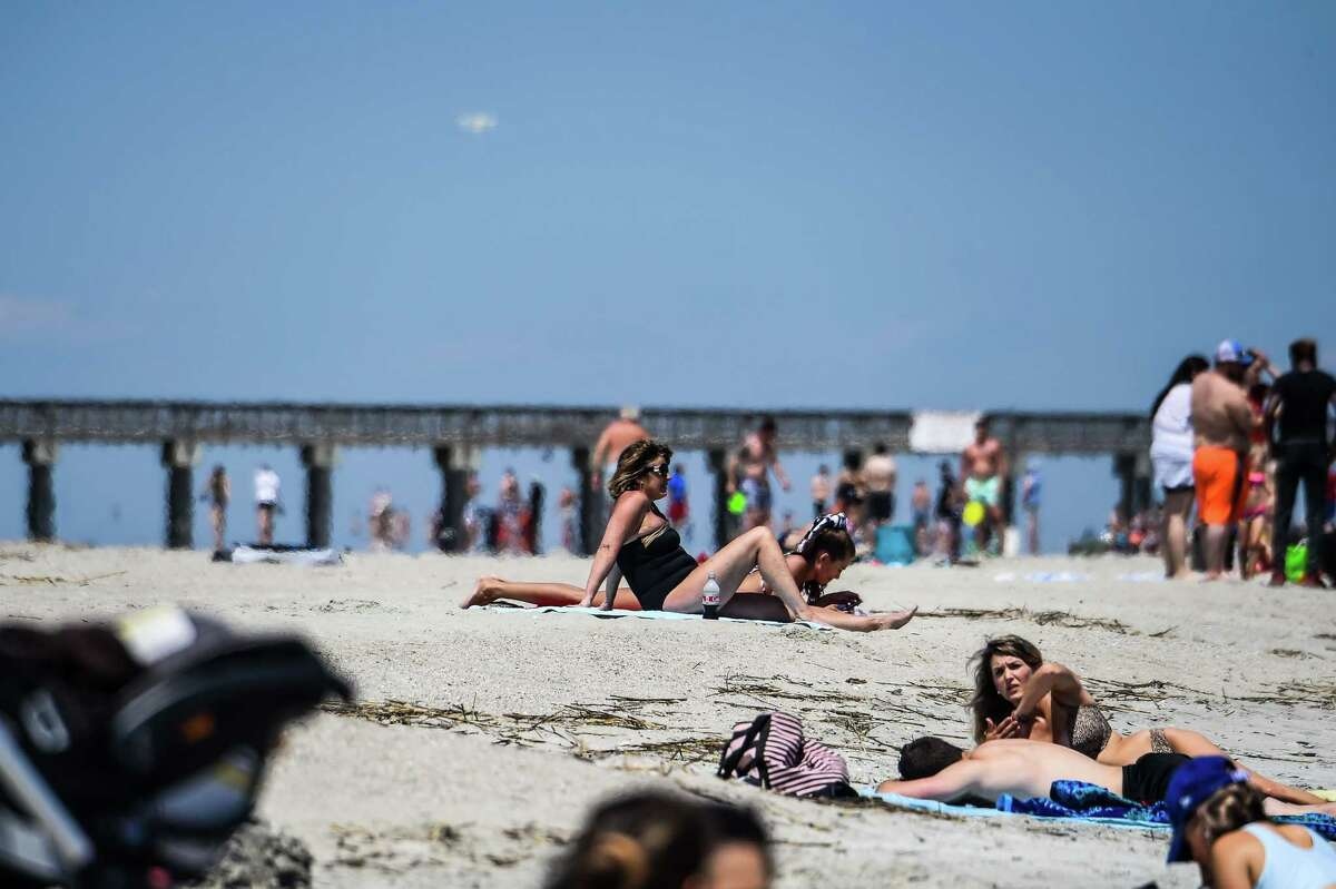 People relax on the Tybee Beach in Tybee Island, Georgia on April 25, 2020. - The Tybee Island city council voted to close the beaches on March 20, but Georgia Governor Brian Kemp issued a statewide shelter-in-place executive order which supersedes all local orders relating to coronavirus and also opened up the state's beaches. (Photo by CHANDAN KHANNA / AFP) (Photo by CHANDAN KHANNA/AFP via Getty Images)
