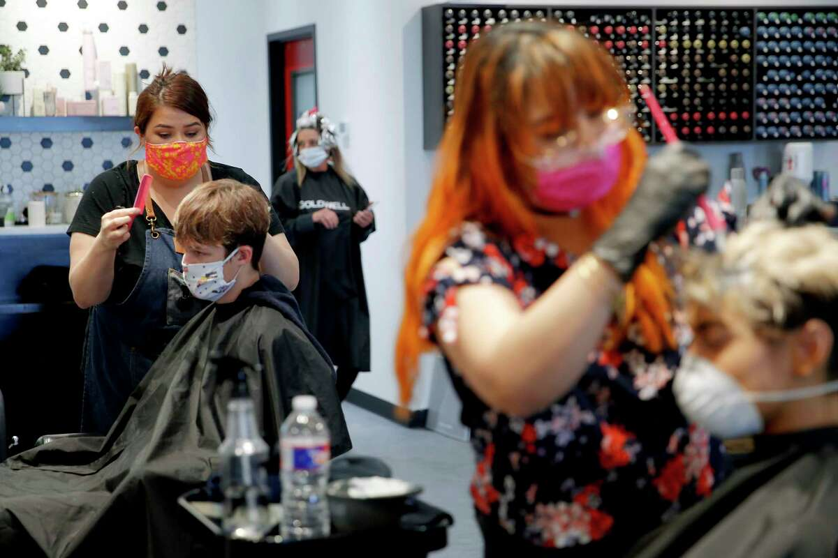 Linzie Castro cuts the hair of Chase Ridgeway inside Azalon Hair Studio and Boutique in Yukon, Okla., Friday, April 24, 2020. The shop was among several allowed to reopen in a loosening of coronavirus-related restrictions. (Bryan Terry/The Oklahoman via AP)