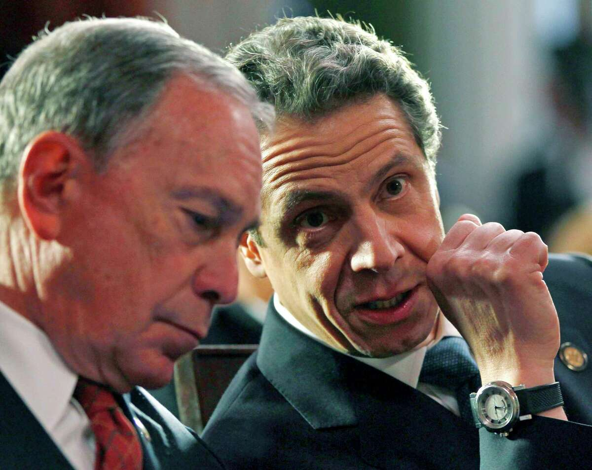 FILE - This March 16, 2012 file photo shows then New York Mayor Michael Bloomberg, left, and New York Gov. Andrew Cuomo at a bill signing ceremony in the Red Room at the Capitol, in Albany, N.Y. Bloomberg will help create a