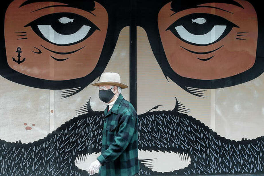 A man wears a mask April 16 while walking by a closed building in San Francisco. Photo: Jeff Chiu | Associated Press