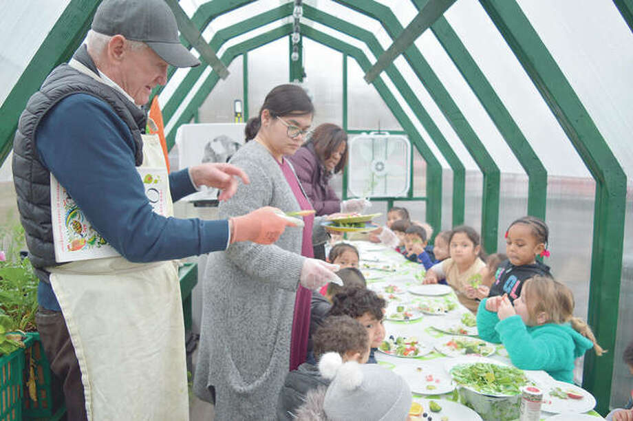 Howard Brosius demonstrates the importance of fresh produce and healthy eating with a carrot inside his mobile greenhouse. Photo: Rachel Ravina | The Reporter (AP)