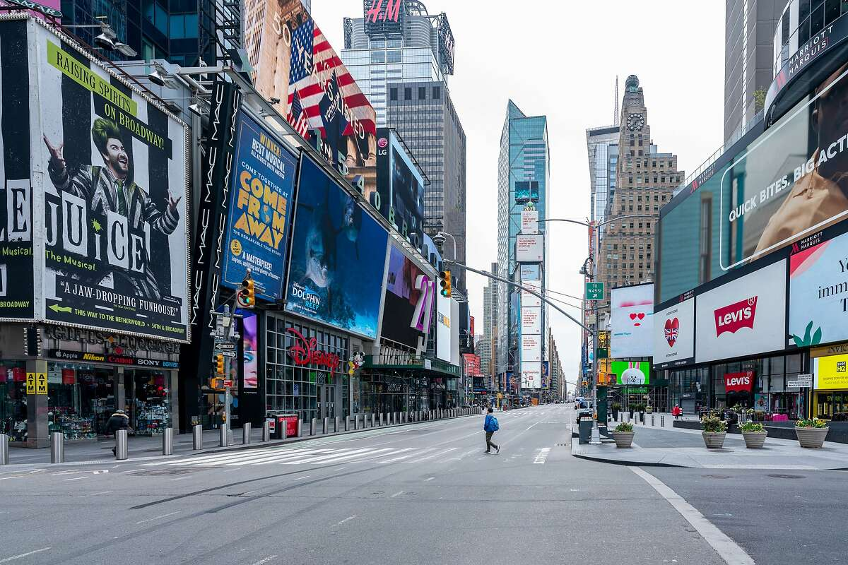 A person crosses the street at very quiet Times Square on April 20, 2020, in New York City. According to the artists' website, the sign serves as commentary on those who decided to leave the city during the height of the pandemic.