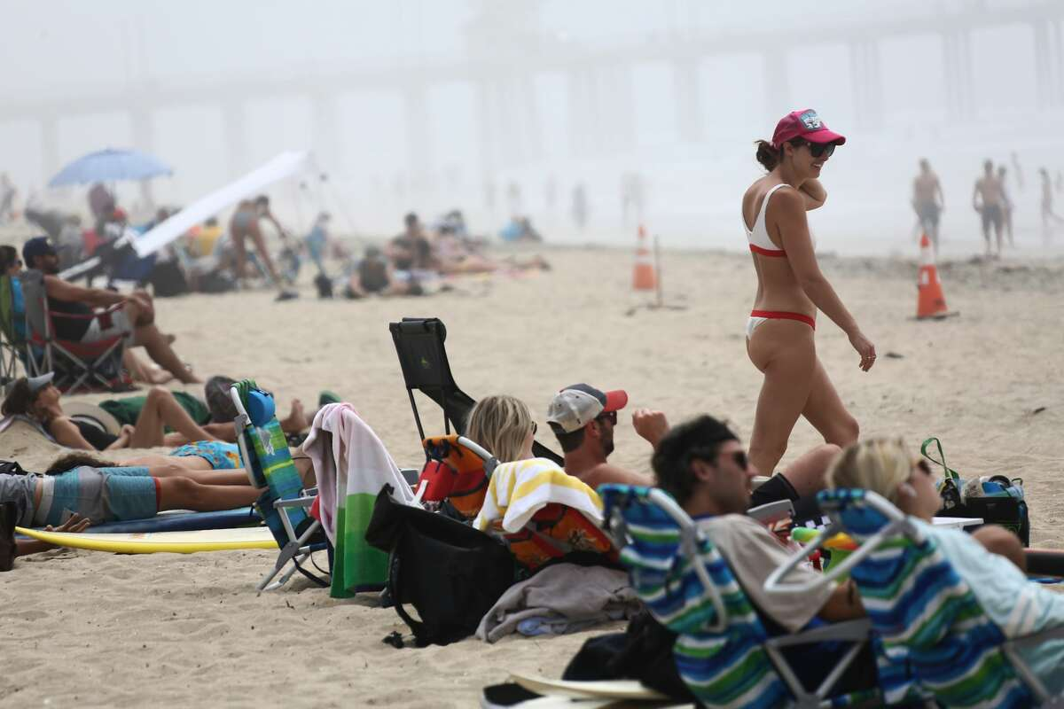 People are seen on Huntington Beach as it remains open during the coronavirus pandemic on April 25, 2020 in Huntington Beach, California.