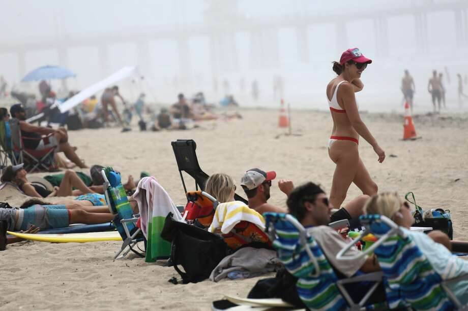 People are seen on Huntington Beach as it remains open during the coronavirus pandemic on April 25, 2020 in Huntington Beach, California. Photo: Tommaso Boddi/Getty Images / 2020 Tommaso Boddi