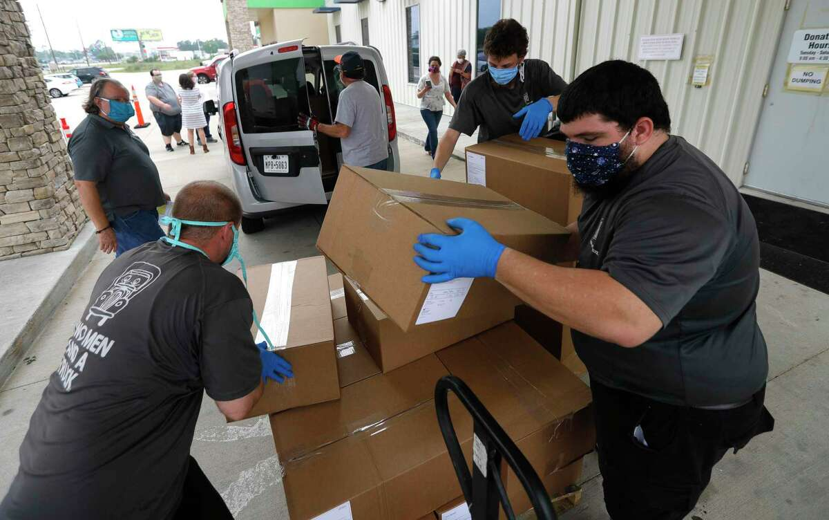 Joshua Lowe, left, Michael Briner, and Kendrall Fessas load masks at the Habitat for Humanity ReStore.