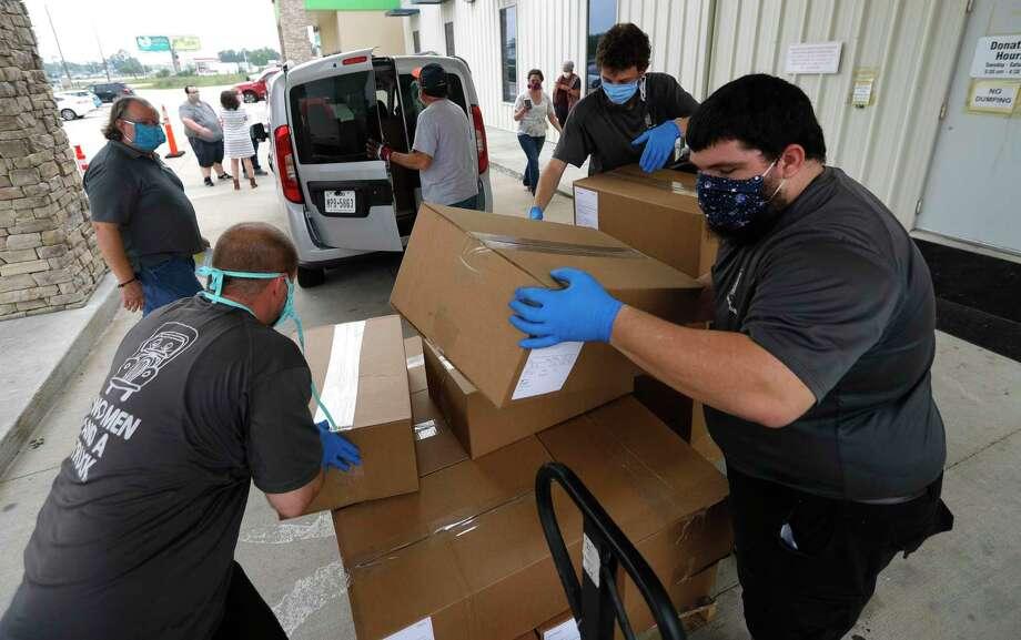 Joshua Lowe, left, Michael Briner, and Kendrall Fessas load masks at the Habitat for Humanity ReStore. Photo: Jason Fochtman, Houston Chronicle / Staff Photographer / 2020 © Houston Chronicle