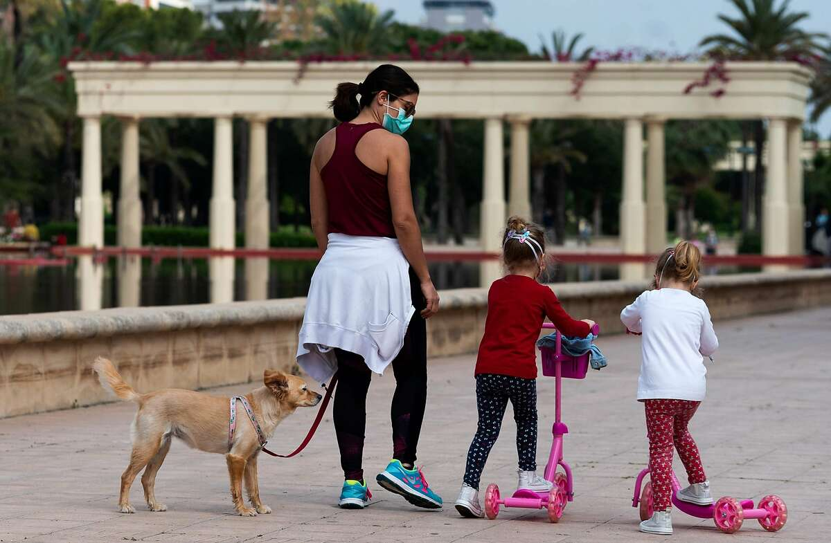A woman and two little girls walk their dog in Valencia on April 26, 2020, amid a national lockdown to prevent the spread of the COVID-19 disease. )