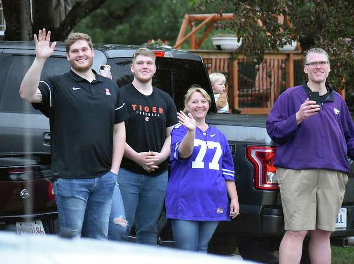 The Kaltmayer family, including Nick on the far left, wave to the parade of cars streaming past their home in Edwardsville after Nick agreed to a unsigned free agent deal with the Miami Dolphins. Kaltmeyer played offensive tackle at Kansas State.