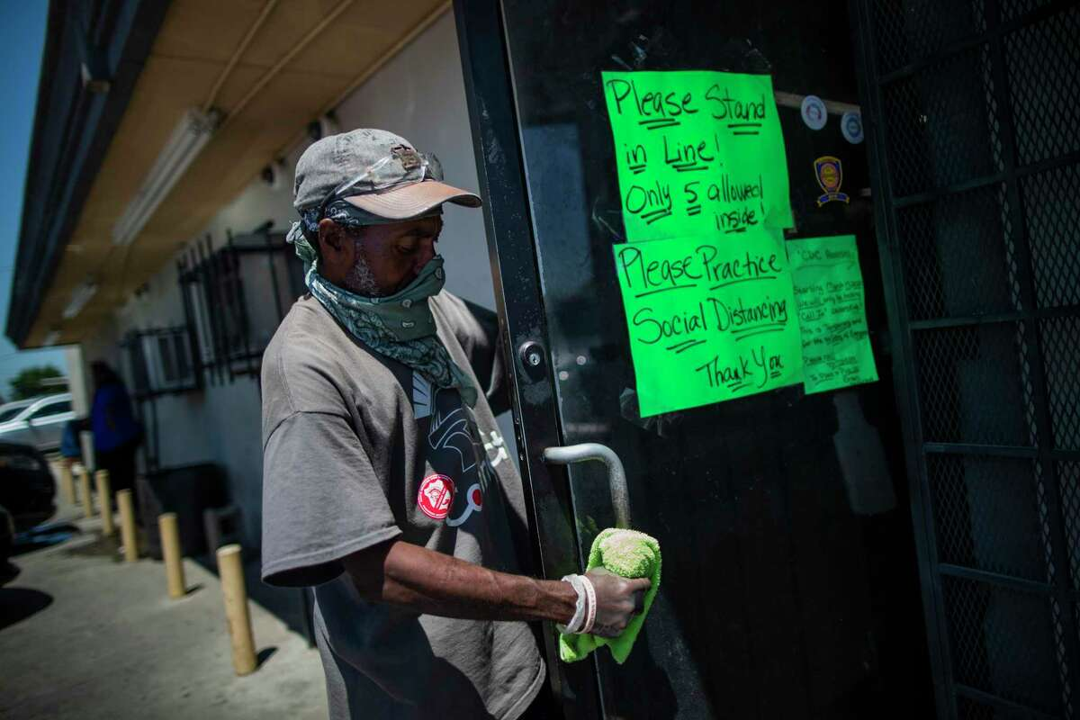Willy Bryant cleans the door handle of TP Seafood Market & Restaurant on April 24 in the Sunnyside neighborhood south of Houston. The market limits the number of shoppers inside to five at a time.