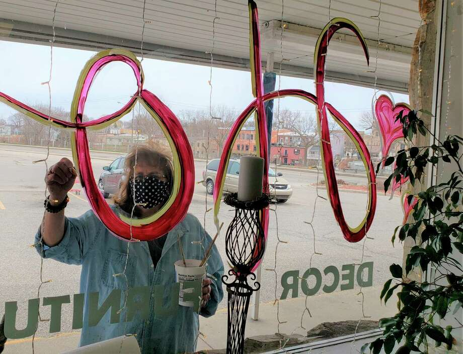 "Denice Leonard, owner of Redeemed Furniture Art and Decor said she wanted to share some hope with Manistee during the COVID-19 pandemic. She could be seen painting the word ""Hope"" with hearts on the store's windows Saturday afternoon at 172 Memorial Drive, Manistee. (Arielle Breen/News Advocate)"