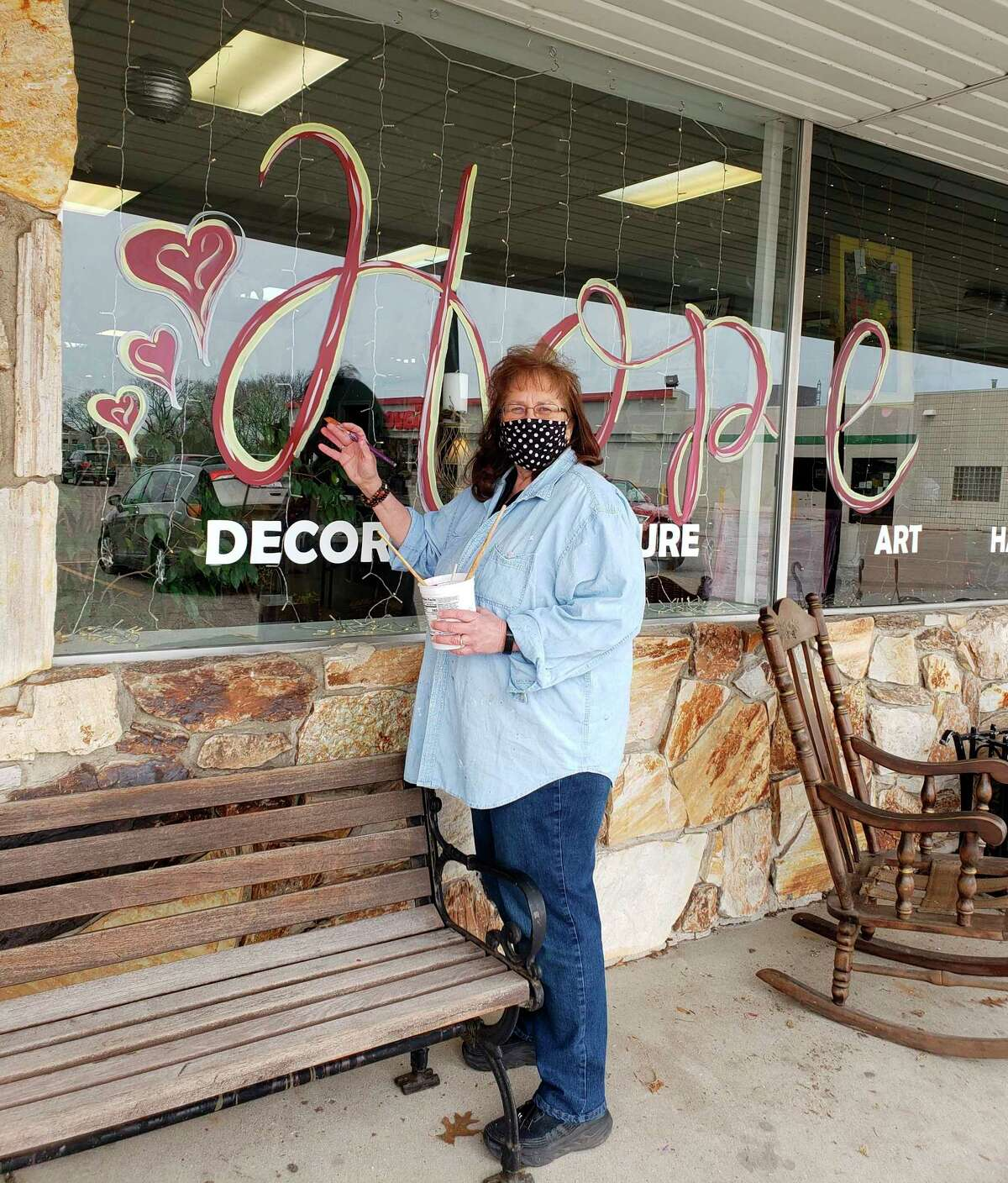 """Denice Leonard, owner of Redeemed Furniture Art and Decor, painted the word """"Hope"""" in bold letters with hearts on the four large storefront windows Saturday afternoon at 172 Memorial Drive, Manistee. (Arielle Breen/News Advocate)"""
