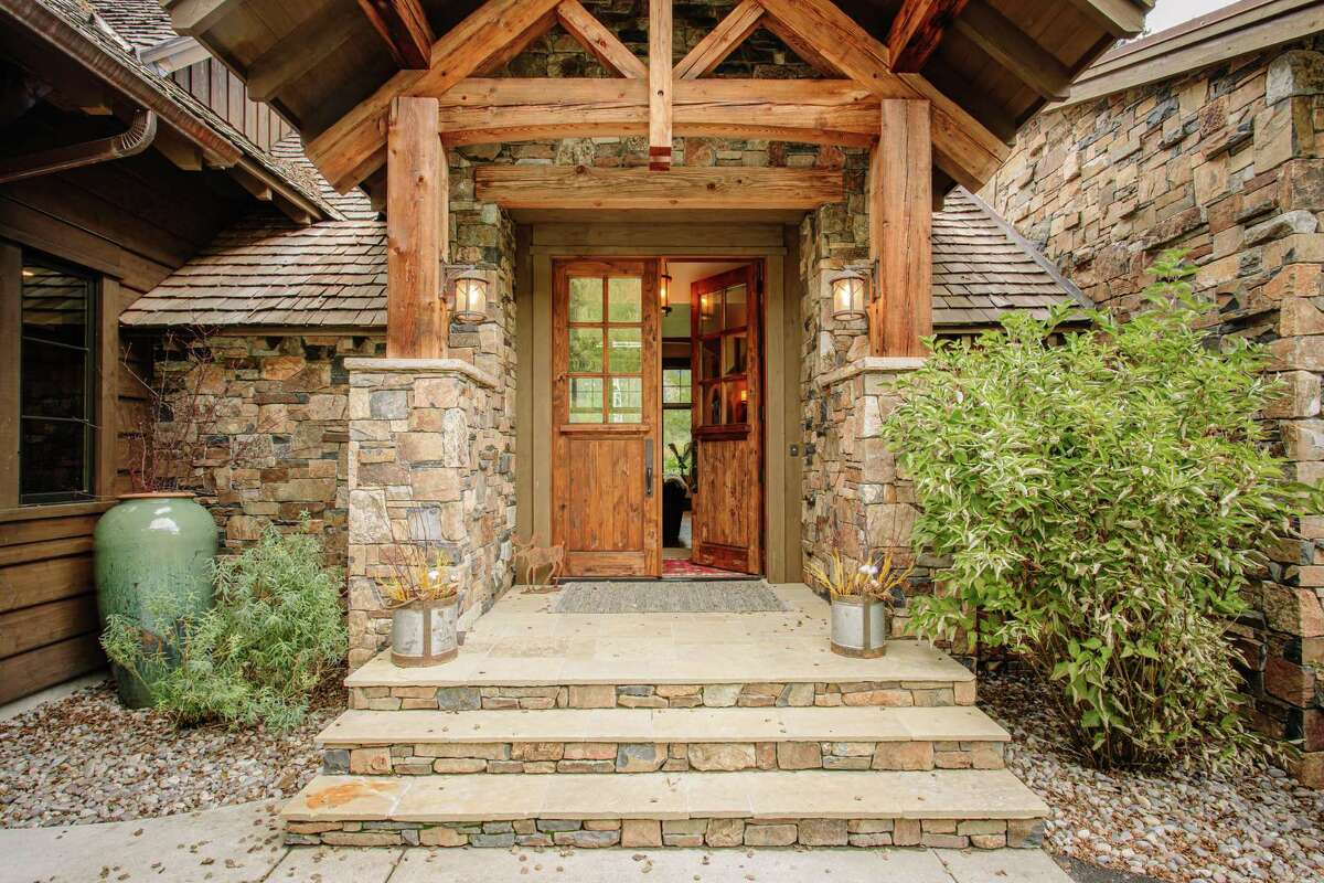 Stacked stone and timber beams fashion the home's portico.