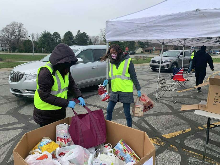 "Adrian Lee, left, and Ellen Hooper of 242 Community Church handle food supplies donated to Hidden Harvest during a ""drive-thru and drop off"" food drive on Saturday, April 25, 2020 in the parking lot of Pat's Food Center in Freeland."