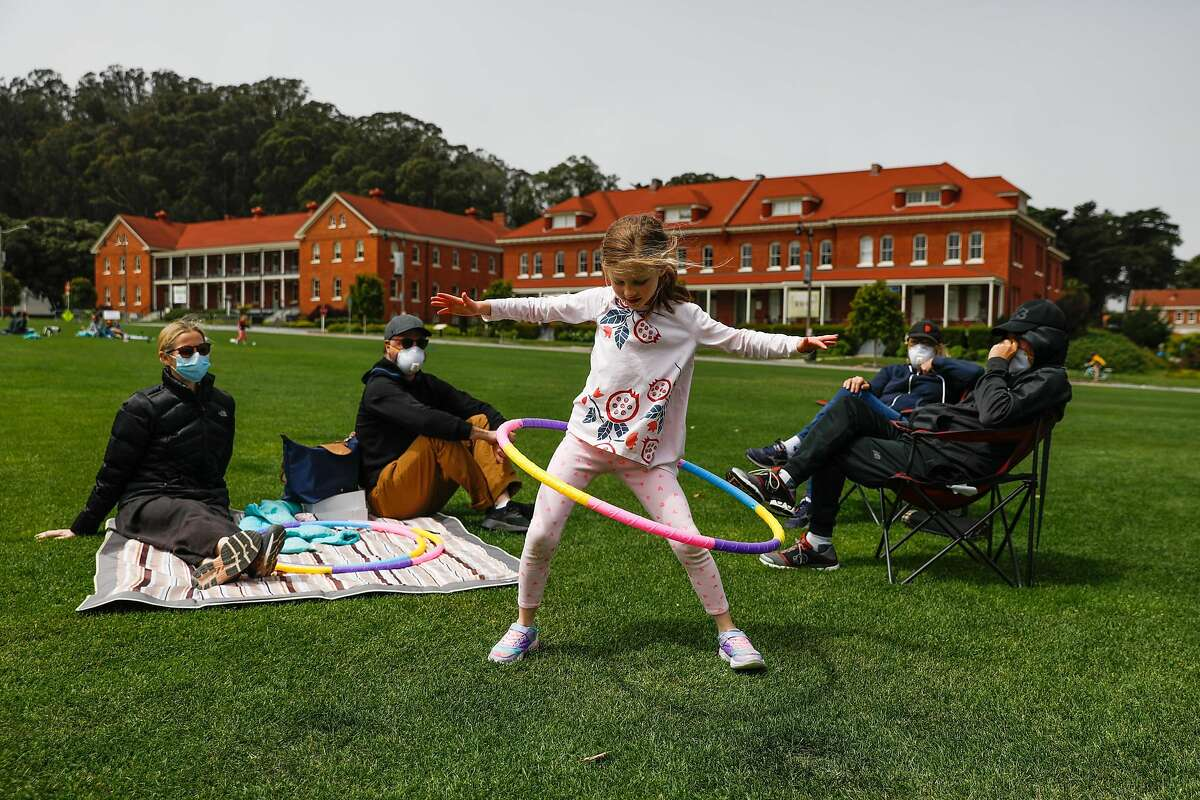 Angie Muscat (center), 6, hula hoops as mom Christina Dam (left), dad Jason Muscat (second from left), grandmother Becky Muscat (second from right) and grandfather Bob Muscat (right) look on at the Main Parade Grounds in the Presidio in San Francisco, California on Sunday, April 26, 2020. Public health officials had feared spring-like weather over the weekend would cause a rush of people to set aside shelter in place mandates and descend upon public parks and beaches, putting themselves at risk to coronavirus exposure.