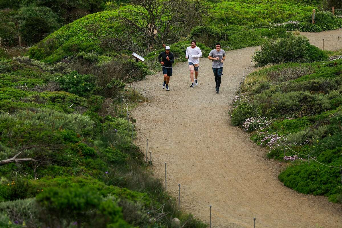 Joggers run through the Presidio in San Francisco, California on Sunday, April 26, 2020. Public health officials had feared spring-like weather over the weekend would cause a rush of people to set aside shelter in place mandates and descend upon public parks and beaches, putting themselves at risk to coronavirus exposure.
