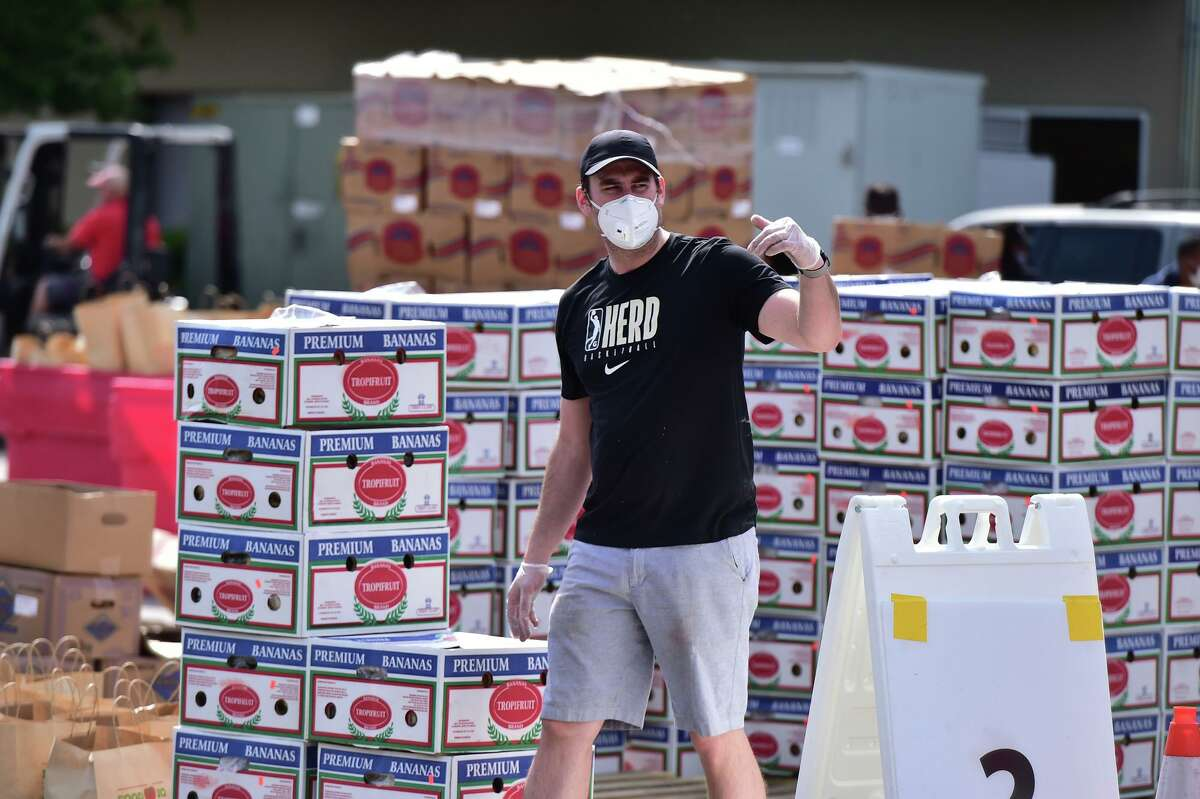 Chase Buford directs traffic during a food distribution event Saturday at the San Antonio Food Bank.