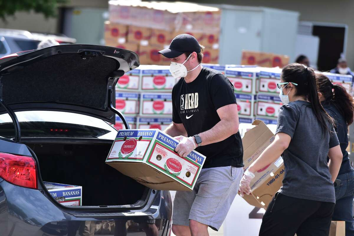 Chase Buford loads a car during a food distribution event Saturday at the San Antonio Food Bank.