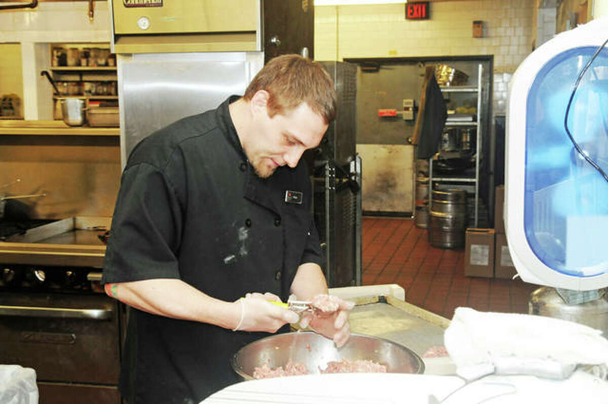 Sous-chef Tyler Biggs prepares an order of meatballs for a carry-out order at the Great Rivers Tap and Grill, part of the Best Western Premier Alton-St. Louis Area Hotel, in Alton.