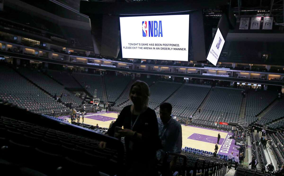 """FILE - In this March 11, 2020 photo, fans leave the Golden 1 Center in Sacramento, Calif., after the NBA basketball game between the New Orleans Pelicans and Sacramento Kings was postponed at the last minute over an """"abundance of caution"""" after a player for the Jazz tested positive for the coronavirus. A person with knowledge of the situation says NBA players will be allowed to return to team training facilities starting Friday, May 1 provided that their local governments do not have a stay-at-home order prohibiting such movement. (AP Photo/Rich Pedroncelli, File)"""