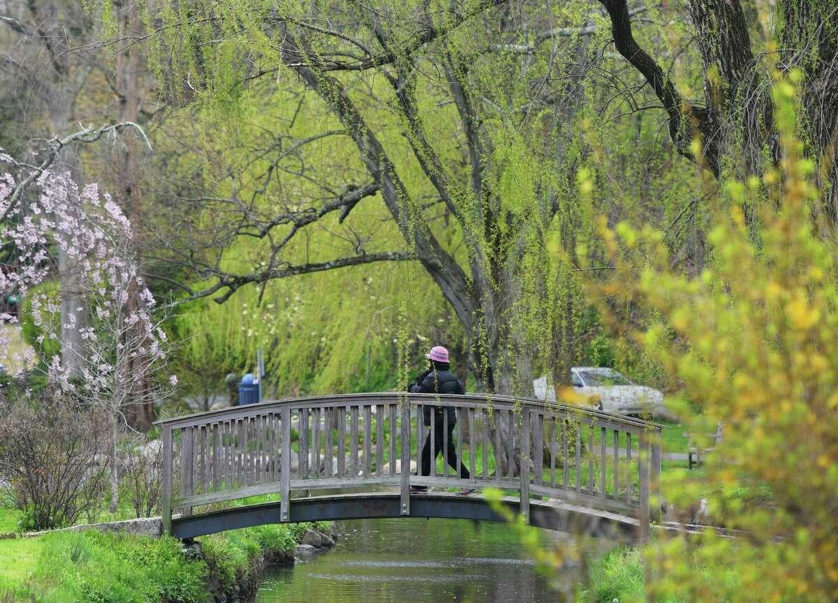 A woman walks across a bridge on a path through Binney Park in Old Greenwich, Conn. Sunday, April 26, 2020.