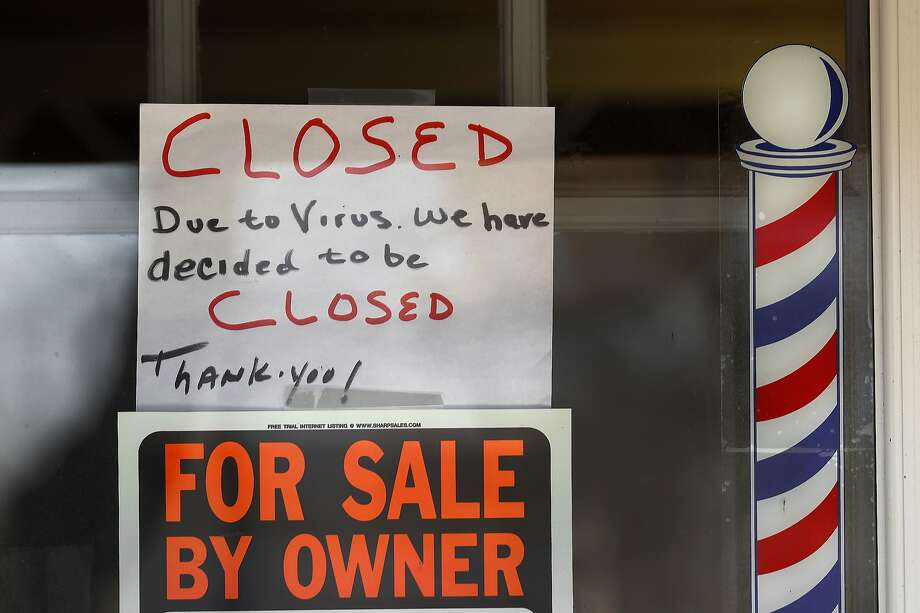 """FILE - In this April 2, 2020 file photo, """"For Sale By Owner"""" and """"Closed Due to Virus"""" signs are displayed in the window of a store in Grosse Pointe Woods, Mich. Photo: Paul Sancya, Associated Press"""