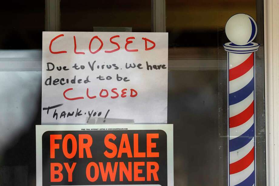 "In this April 2, 2020 file photo, ""For Sale By Owner"" and ""Closed Due to Virus"" signs are displayed in the window of a store in Grosse Pointe Woods, Mich. Business filings under Chapter 11 of the federal bankruptcy law rose sharply in March, and attorneys who work with struggling companies are seeing signs that more owners are contemplating the possibility of bankruptcy. Government aid my simply be too little too late.