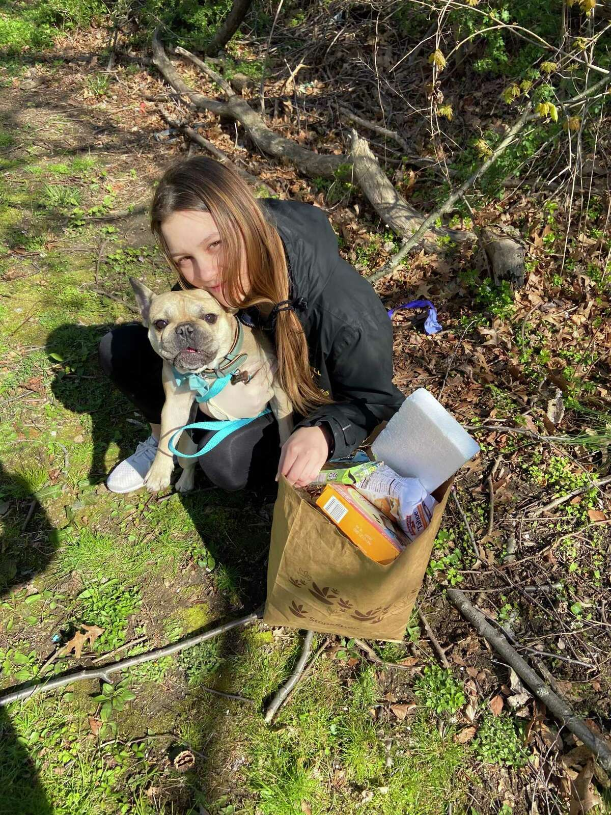 Kateryna Pekar, a Westhill High School student, picks up trash with her dog on recently, on Earth Day. Her classmate, Jack Engel, created his own climate organization, titled, Clean2BGreen. The mission of the organization is to pick up at least one piece of trash every day and inspire others to do the same.