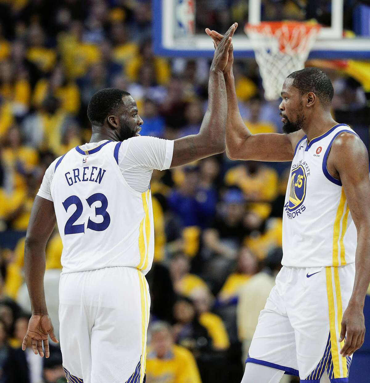 Golden State Warriors' Draymond Green and Kevin Durant high five in the third quarter during game 1 of round 2 of the Western Conference Finals between the Golden State Warriors and the New Orleans Pelicans at Oracle Arena on Saturday, April 28, 2018 in Oakland, Calif.