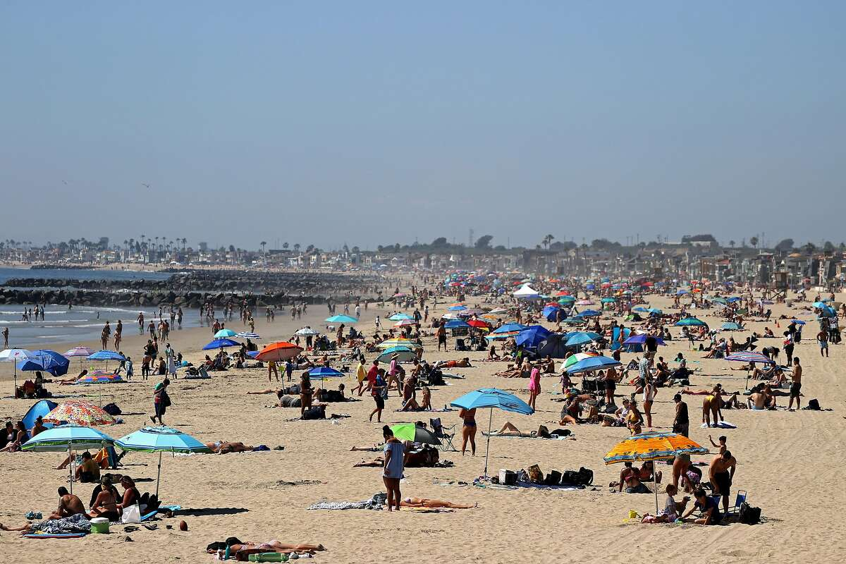People are seen gathering on the beach north of Newport Beach Pier on April 25, 2020 in Newport Beach, California. Southern California is expecting summer like weather this weekend as social distancing and beach closures in neighboring counties continue due to the coronavirus (COVID-19).