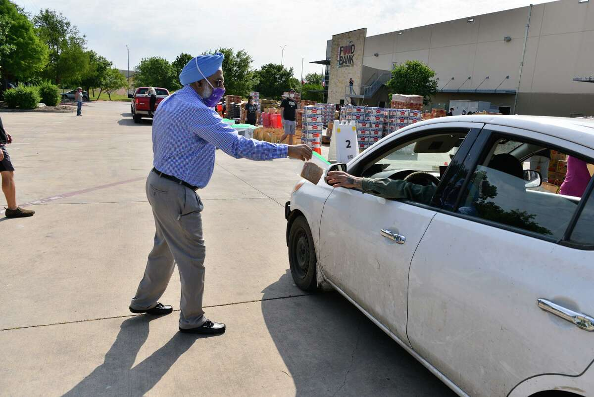 G.P. Singh of the Sikh Dharamsal of San Antonio hands a peanut and jelly sandwich to a person in line Saturday during a food distribution at the San Antonio Food Bank.