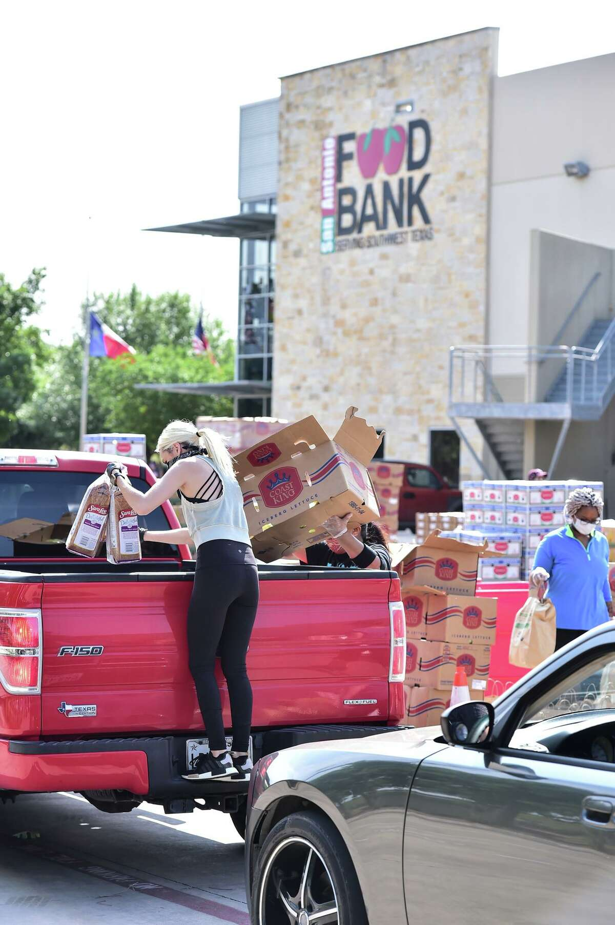 """Volunteers load a truck Saturday during a food distribution at the San Antonio Food Bank. """"To Go For Good"""" has set a goal of raising $150,000 to help the Food Bank, which is feeding 120,000 people weekly during the coronavirus pandemic, more than double what it did before COVID-19."""