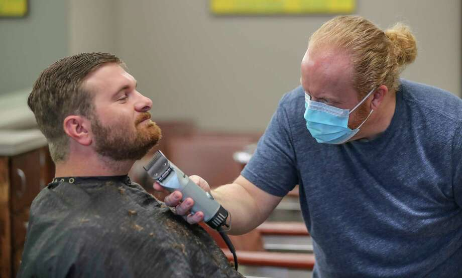 Barber and owner of Chris Edwards wears a mask and cuts the hair of customer David Boswell at Peachtree Battle Barber Shop in Atlanta on Friday, April 24, 2020. The first phase of Georgia Gov. Brian Kemp's plan to reopen Georgia during the coronavirus pandemic included haircut shops and gyms, though not all chose to open their doors. (John Spink/Atlanta Journal-Constitution via AP) Photo: JOHN SPINK, AP / © 2020 Atlanta Journal-Constitution