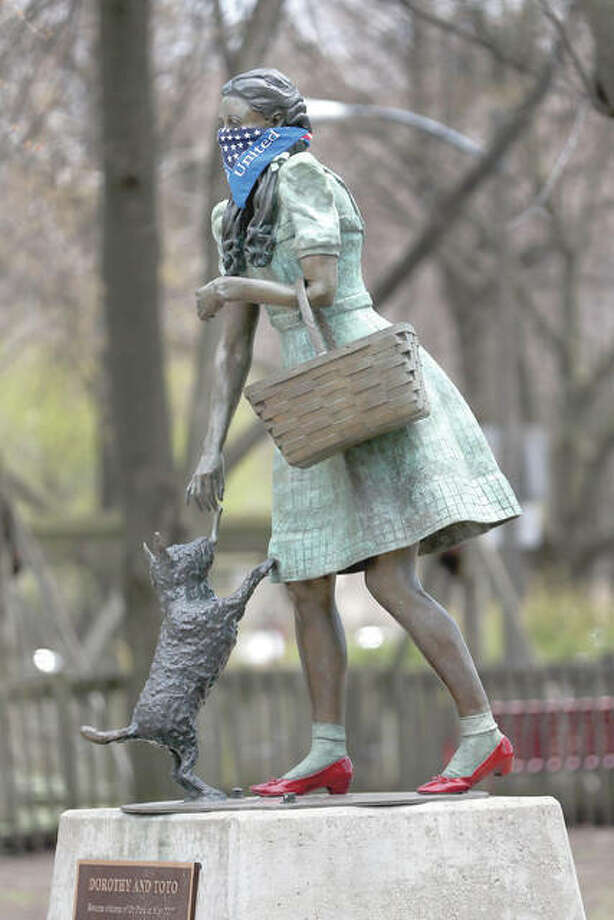 A protective bandana is placed on a statue of Dorothy — and her little dog Toto, too — in Chicago's Oz Park.