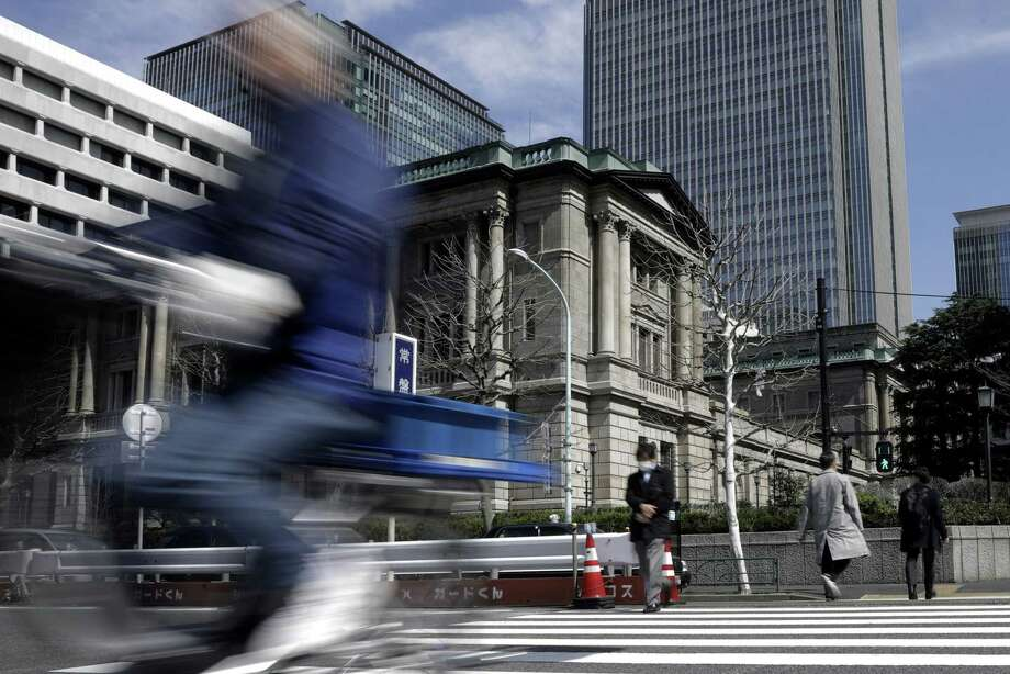 Pedestrians cross a road in front of the Bank of Japan headquarters in Tokyo on March 16, 2020. Photo: Bloomberg Photo By Kiyoshi Ota. / © 2020 Bloomberg Finance LP
