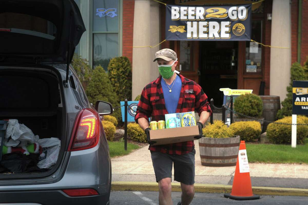 Ted Pert, taproom manager at Two Roads Brewing Company, delivers beer order to a waiting vehicle outside the brewery in Stratford, Conn. April 23, 2020. While Two Road's taproom remains closed, the brewery is open for online orders and curbside pickup.
