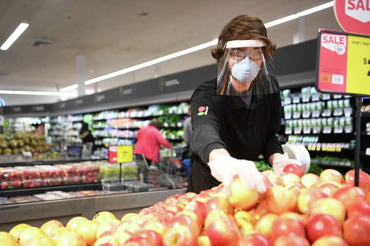 A Stop & Shop employee stocks produce in April 2020 at a store in Simsbury, Conn. Gov. Ned Lamont ordered all business establishments to provide employees masks as of April 20 and until further notice during the 2020 pandemic of the novel coronavirus COVID-19. (Photo courtesy Stop & Shop)