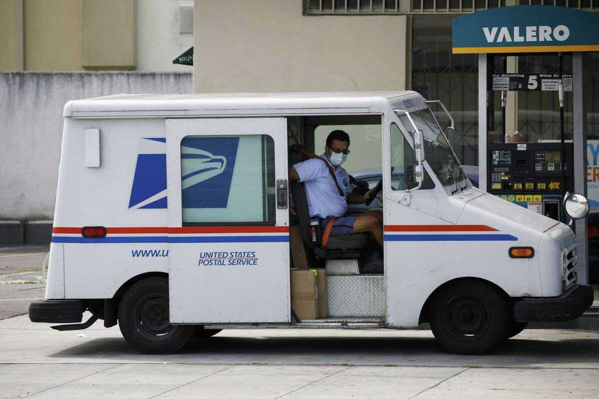 A U.S. Postal Service (USPS) mail carrier wearing a protective mask closes a vehicle door after refueling in Hawthorne, California, U.S., on Monday, April 20, 2020. Los Angeles county issued orders requiring residents and workers towear face coverings in essential businesses. Photographer: Patrick T. Fallon/Bloomberg